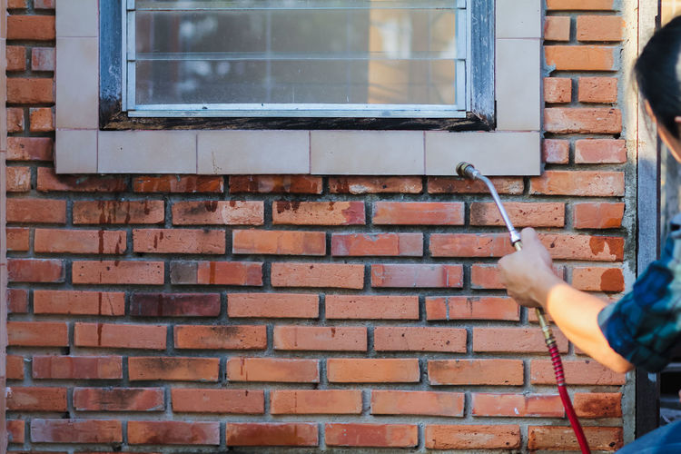 Low section of person holding window on brick wall