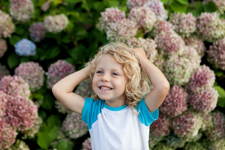 Smiling girl standing against pink flowering plants