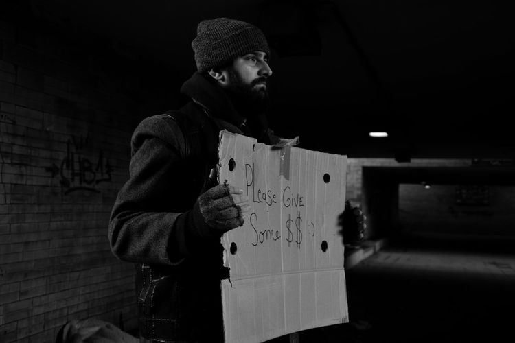 Homeless man holding banner with text