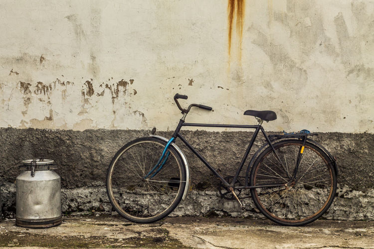Bicycle parked by old building on street