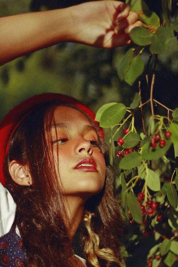 Teenage Girl Looking At Berries On Plant