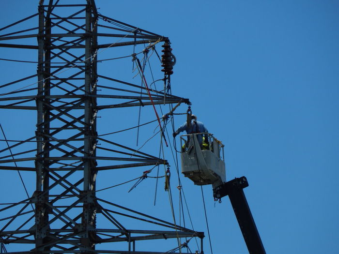 Worker on cherry picker repairing electricity pylon against clear blue sky