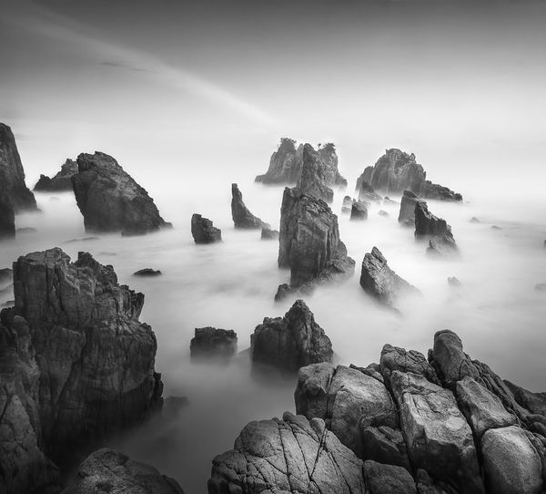 Scenic View Of Rock Formations Against Sky During Foggy Weather