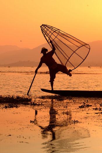 Man fishing in lake at sunset