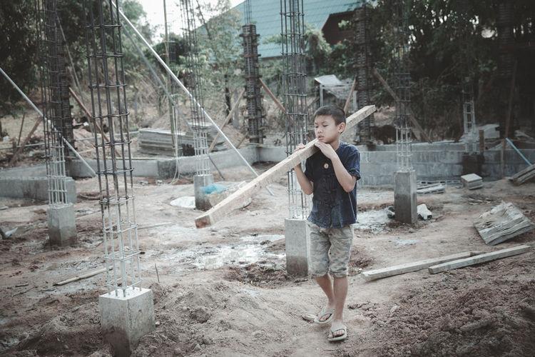 Full length portrait of boy standing against trees