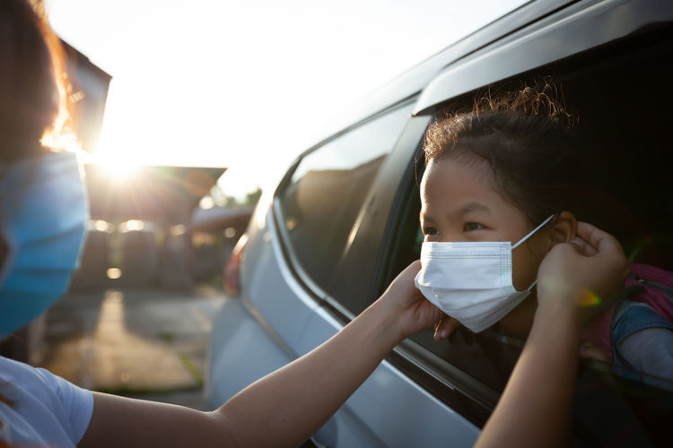 Mother getting daughter dressed with face mask in car