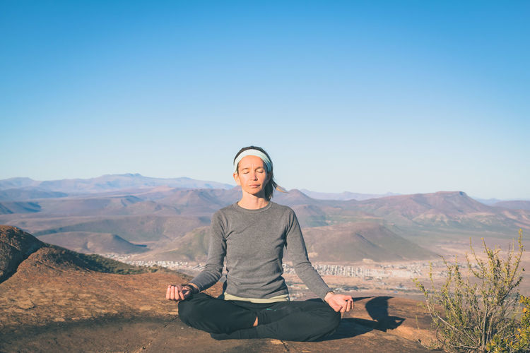 Calm Meditation Mountain View Nature Reflection Spirituality Vacations Beauty In Nature Clear Sky Landscape Lifestyles Lotus Position Meditate Meditate, Contemplate, Think, Consider, Ponder, Muse, Reflect, Deliberate Mid Adult Women Mountain Outdoors Portrait Real People Sitting Tranquil Scene