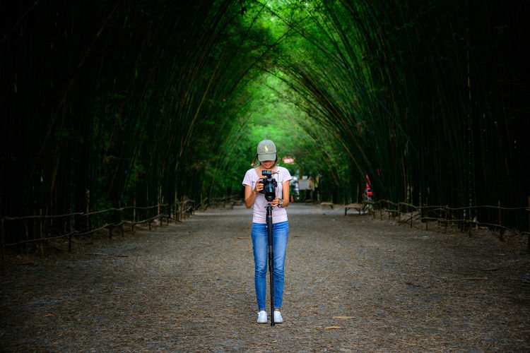 Woman using camera while standing on road against trees