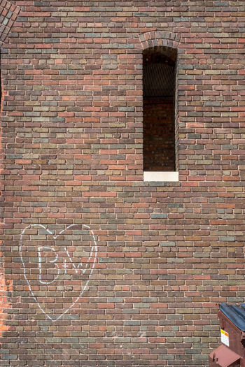 old industrial brick building with heart and initials spray painted on wall next to dumpster Brick Wall Industrial Initial Inner City Life Love Romance Rustic Alley Alleyway Architecture Brick Wall Building Exterior Built Structure Day Dumpster Grafitti Heart No People Outdoors Spray Paint Urban Window Windows