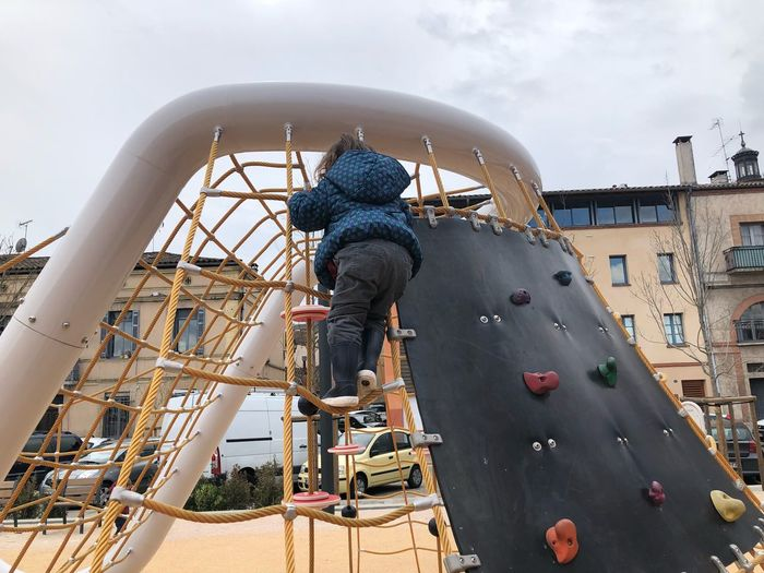 Rear View Of Girl Climbing On Play Equipment At Playground