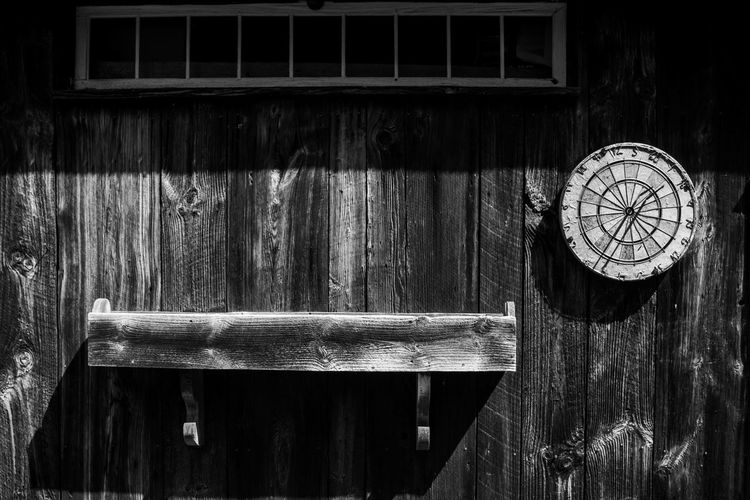 Close-up of wooden clock hanging on old door