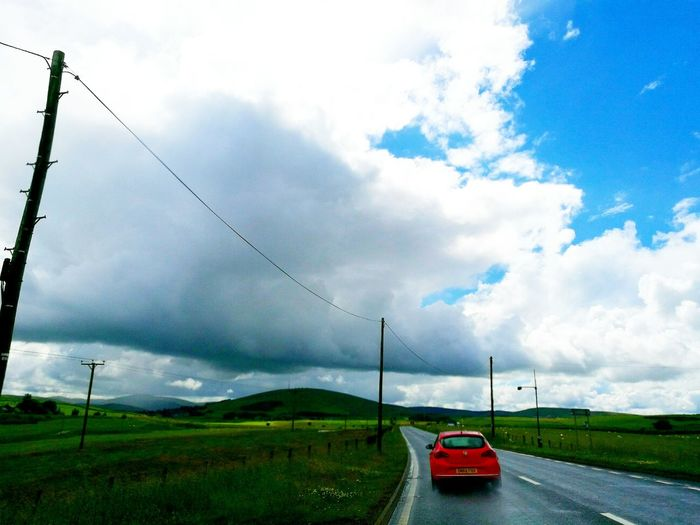 Red Car Blue Sky And Clouds Scottish Highlands going home.