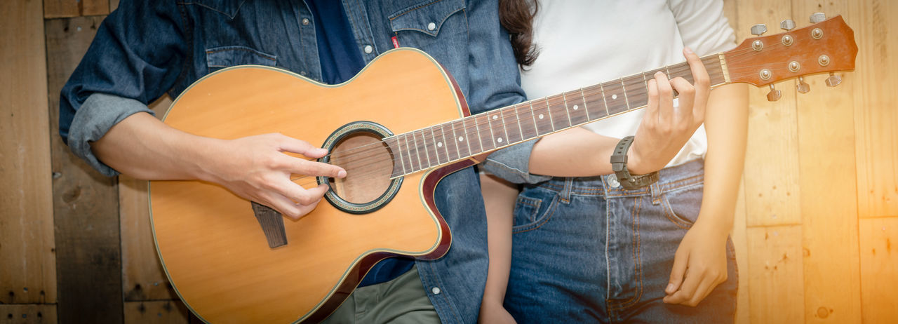 Midsection of man playing guitar by woman standing