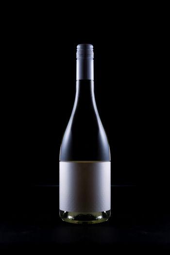 Glass of bottle against black background