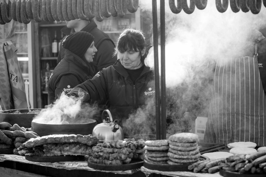 PERNIK, BULGARIA - JANUARY 26, 2018: Woman smiles and cooks steamy meal outdoors in the sunny winter day at the annual International Festival of Masquerade Games Surva, black and white image Black & White Cooking Cooking At Home Event Games Kukeri Kukeri, Bulgaria Sausages Sausages! Smile ✌ Smoke Smoky Steam Steamy Woman Black And White Black And White Photography Cooking Outdoors Festival Food Masquerade Sausage Smile Smiling Surva