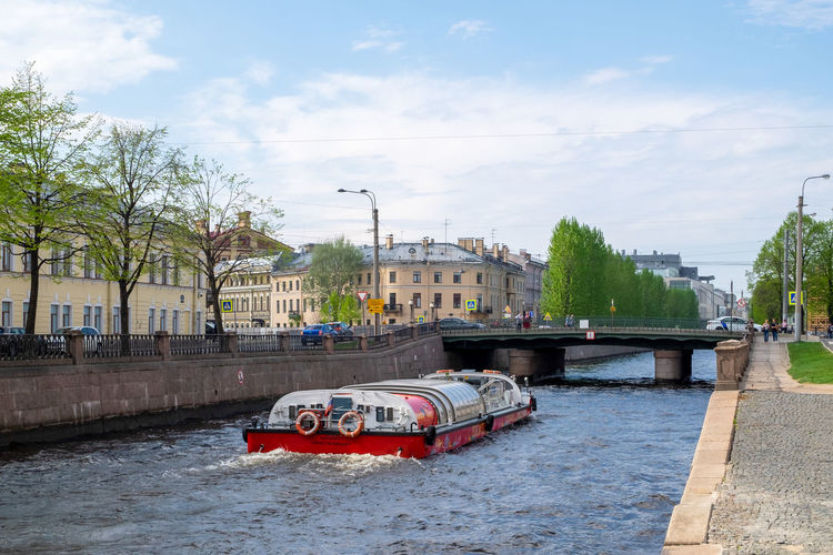 Boat in river by city against sky