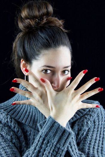 Portrait of beautiful woman showing nails while standing against black background