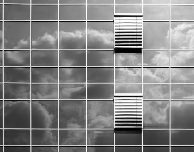Cloudy sky reflecting on glass building with window