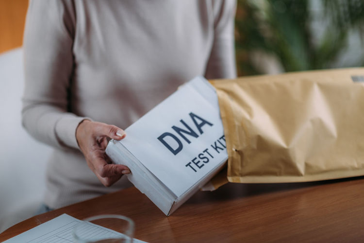 Midsection of woman putting dna kit in envelope