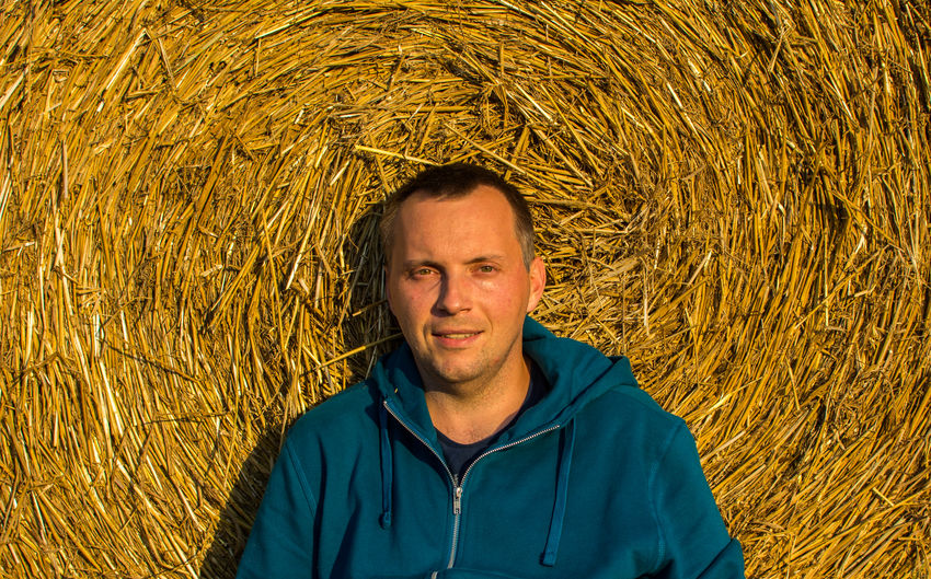Directly above portrait of mid adult man lying on hay bale