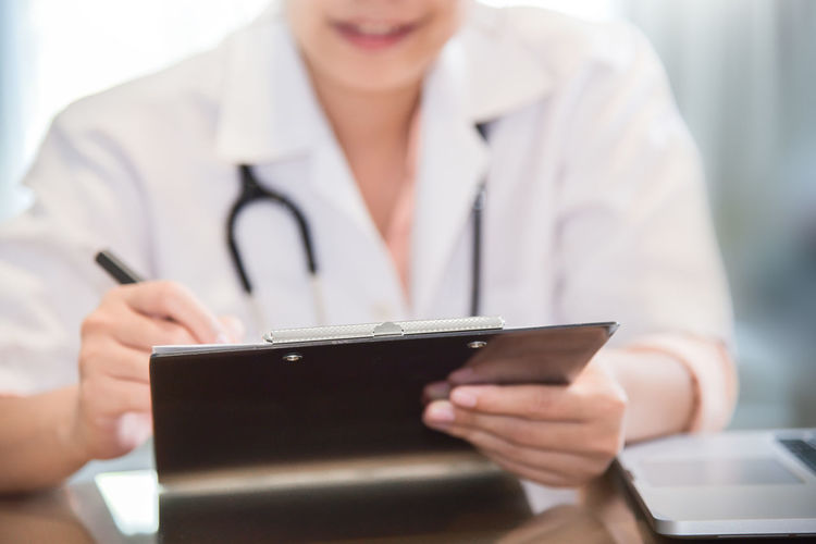 Close up on female doctor writing something on clipboard, prescription, paperwork,patient checklist paper or application form at a hospital. Adult Asian  Care Copy Space Diagnosis Doctor  Hospital Man Woman Working Clinic Clipboard Consulting Digital Exam Healthy Medical Note Patient Stethoscope