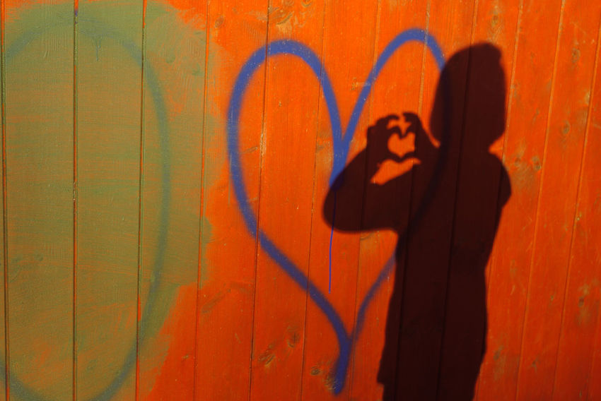 Wall - Building Feature One Person Graffiti Real People Shadow Standing Wall Lifestyles Waist Up Art And Craft Creativity Emotion Leisure Activity Spray Paint Built Structure Architecture Orange Color Casual Clothing Three Quarter Length Obscured Face Focus On Shadow Heart Heart Shape Girl Autumn Mood 50 Ways Of Seeing: Gratitude