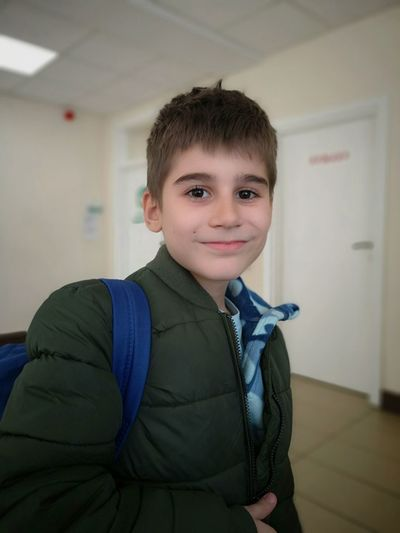Portrait of boy smiling while standing in waiting room
