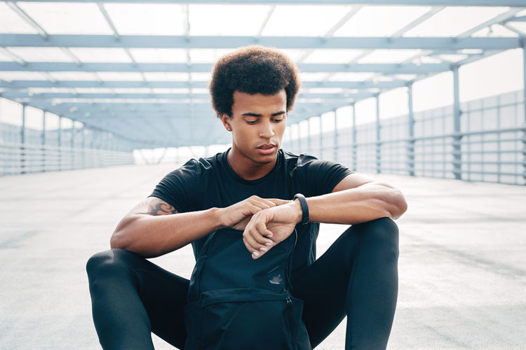 Young man looking away while sitting on wall