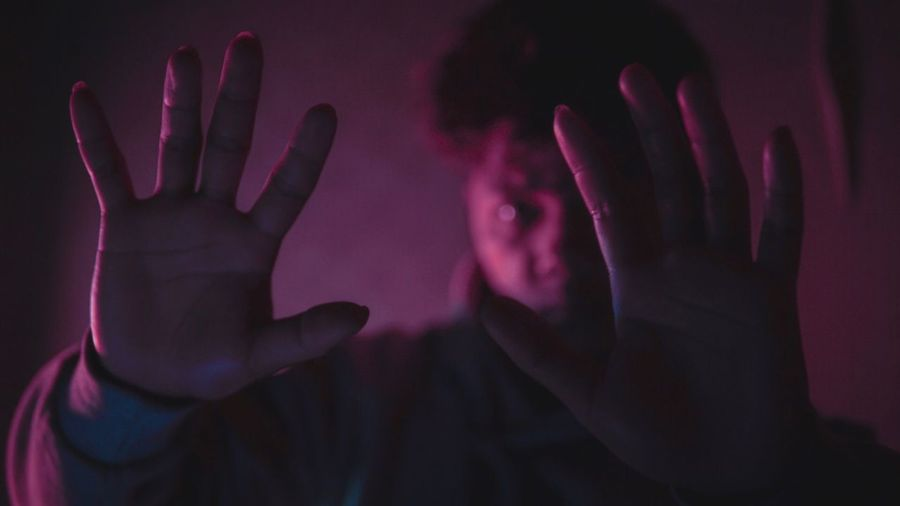 Close-up of man gesturing in darkroom