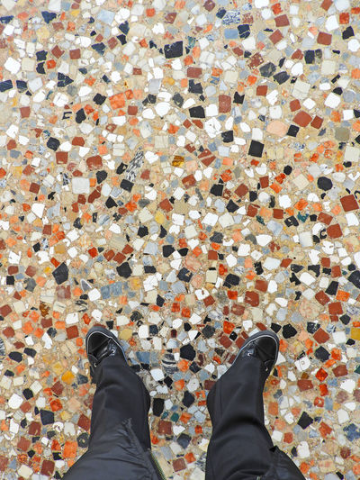 Low section of man standing on tiled floor
