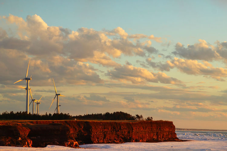 Scenic view of wind turbines by the sea at sunset