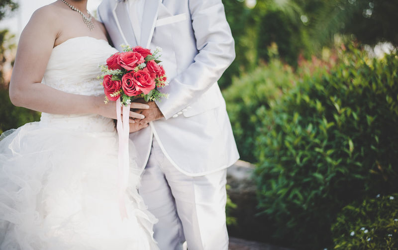 Midsection of bride and bridegroom holding bouquet on field