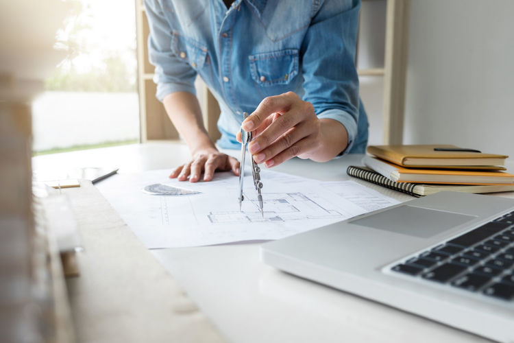 Midsection of female engineer drawing blueprint in office