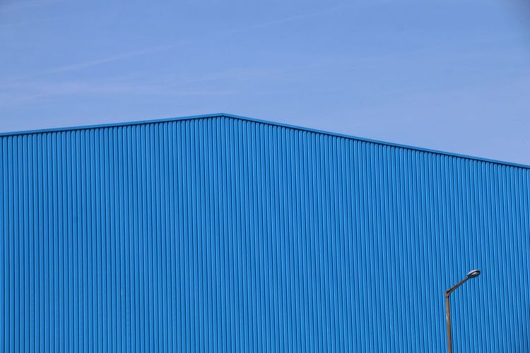 Low Angle View Of Blue Factory Against Sky