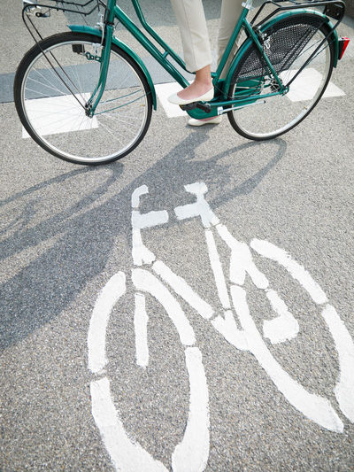 Shadow of man riding bicycle on road