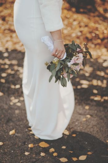 Low section of bride holding white flower