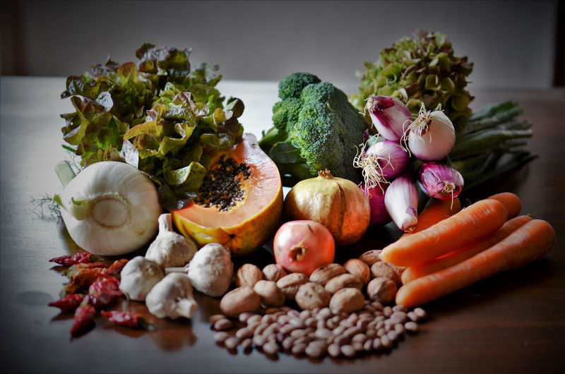 Fresh vegetables, fruits and nuts on a table.
