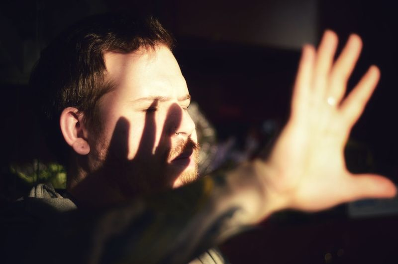 Close-up of young man shielding eyes at home