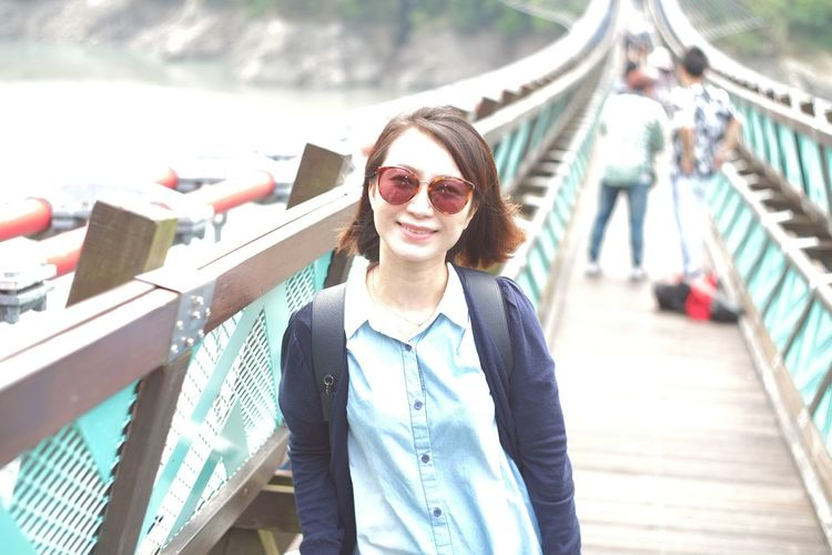 Smiling woman standing on footbridge