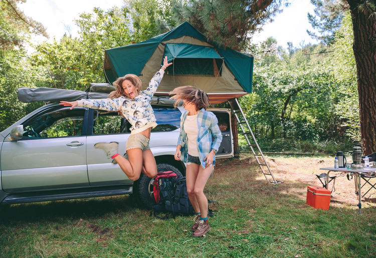 Happy Friends Jumping At Campsite In Forest