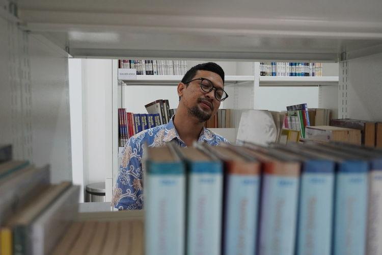 Young man seen through book shelf