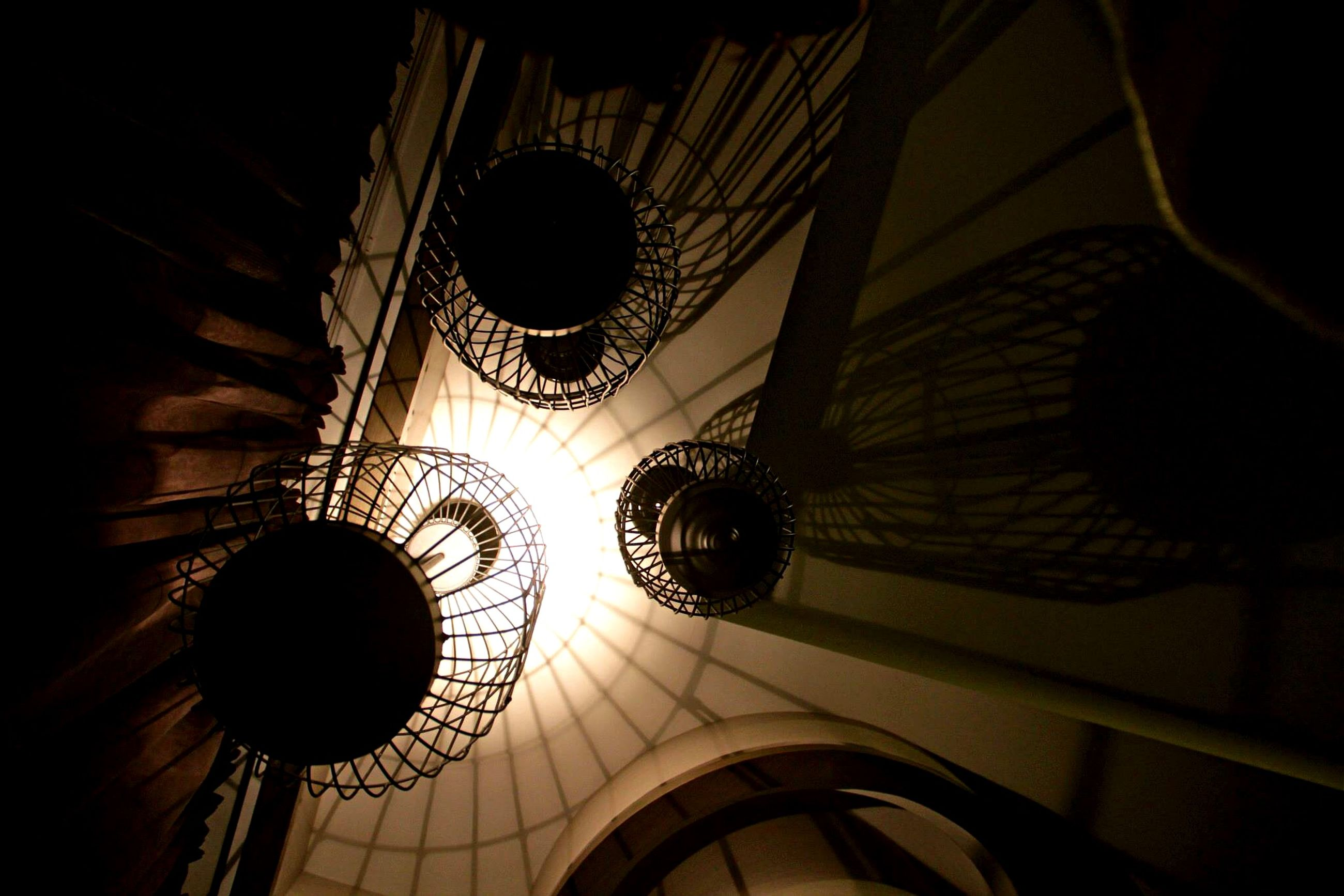 low angle view, illuminated, indoors, lighting equipment, hanging, architecture, ceiling, built structure, night, circle, electricity, electric lamp, pattern, electric light, no people, directly below, design, decoration, geometric shape, chandelier