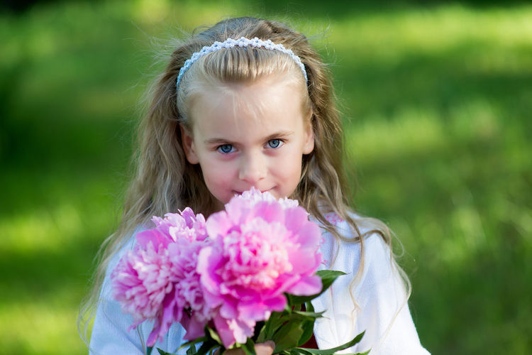 Portrait of a small girl with peonies Beauty In Nature Blond Hair Child Childhood Close-up Cute Day Flower Flower Head Focus On Foreground Fragility Freshness Girls Grass Innocence Looking At Camera Nature One Girl Only One Person Outdoors People Pink Color Portrait Real People Smiling