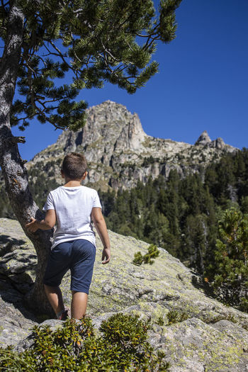 Rear view of man standing on rock against mountain