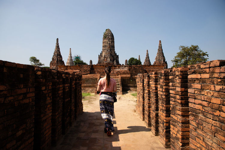 Rear view of woman walking towards temple old ruins