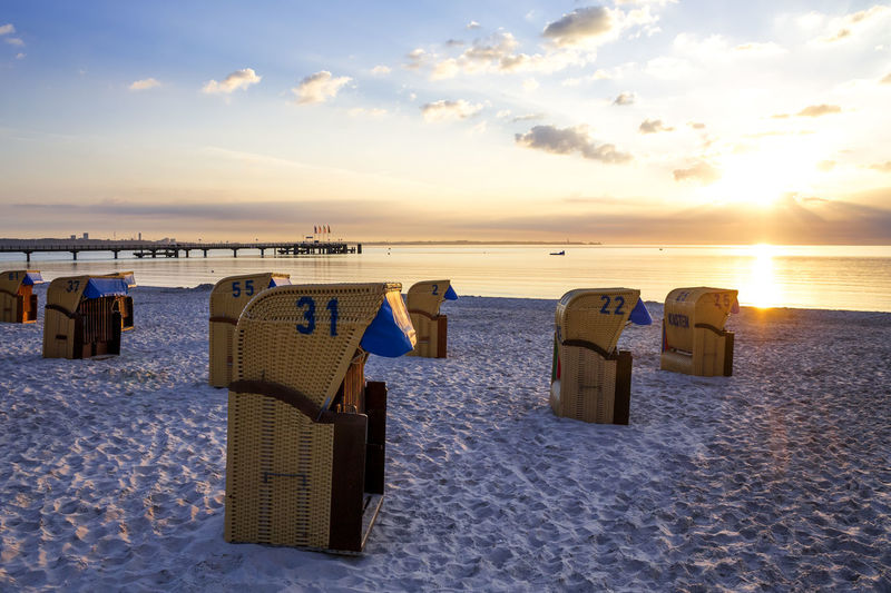 Hooded chairs at beach against sky during sunset
