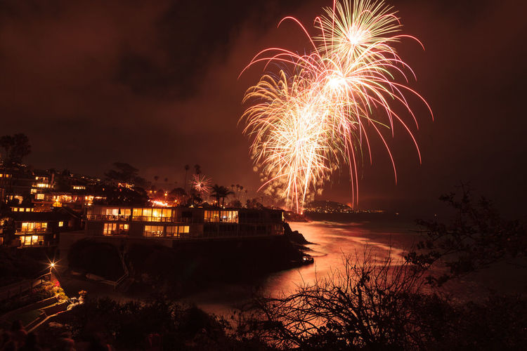 Illuminated fireworks over beach against sky in city at night
