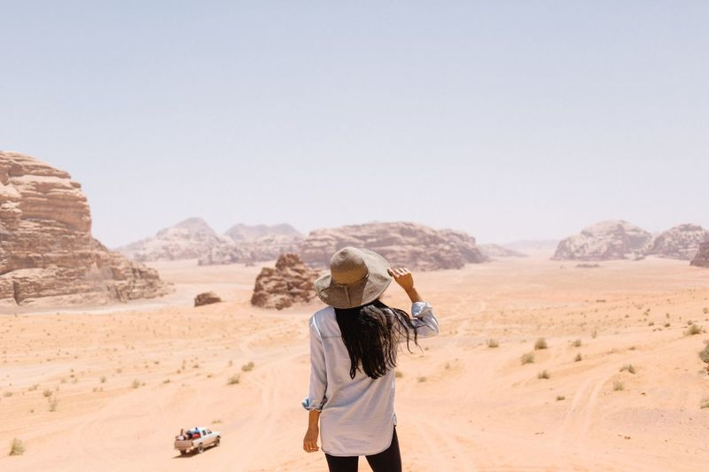 Rear view of woman standing at desert against clear sky