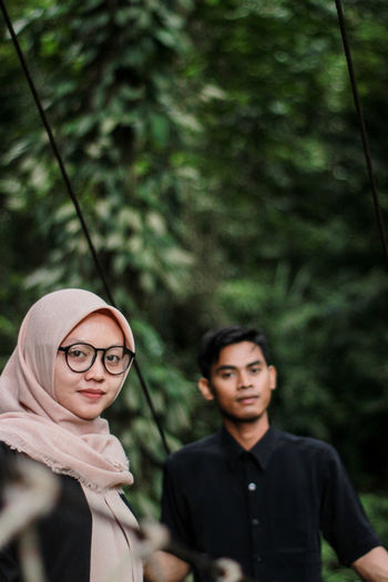Portrait of young man with girlfriend standing on footbridge in forest