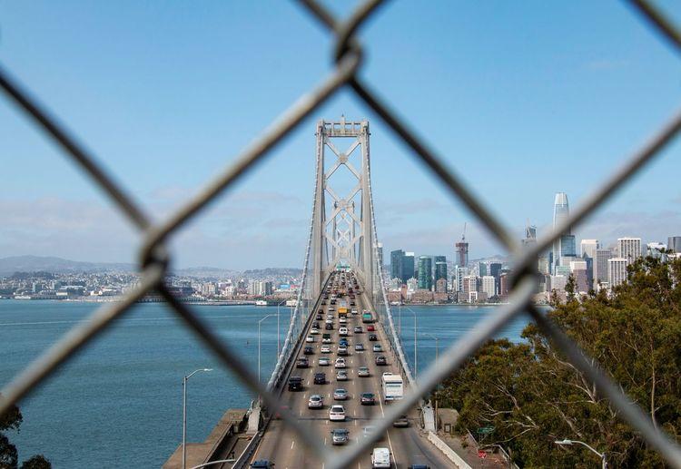 San francisco-oakland bay bridge over sea seen through chainlink fence
